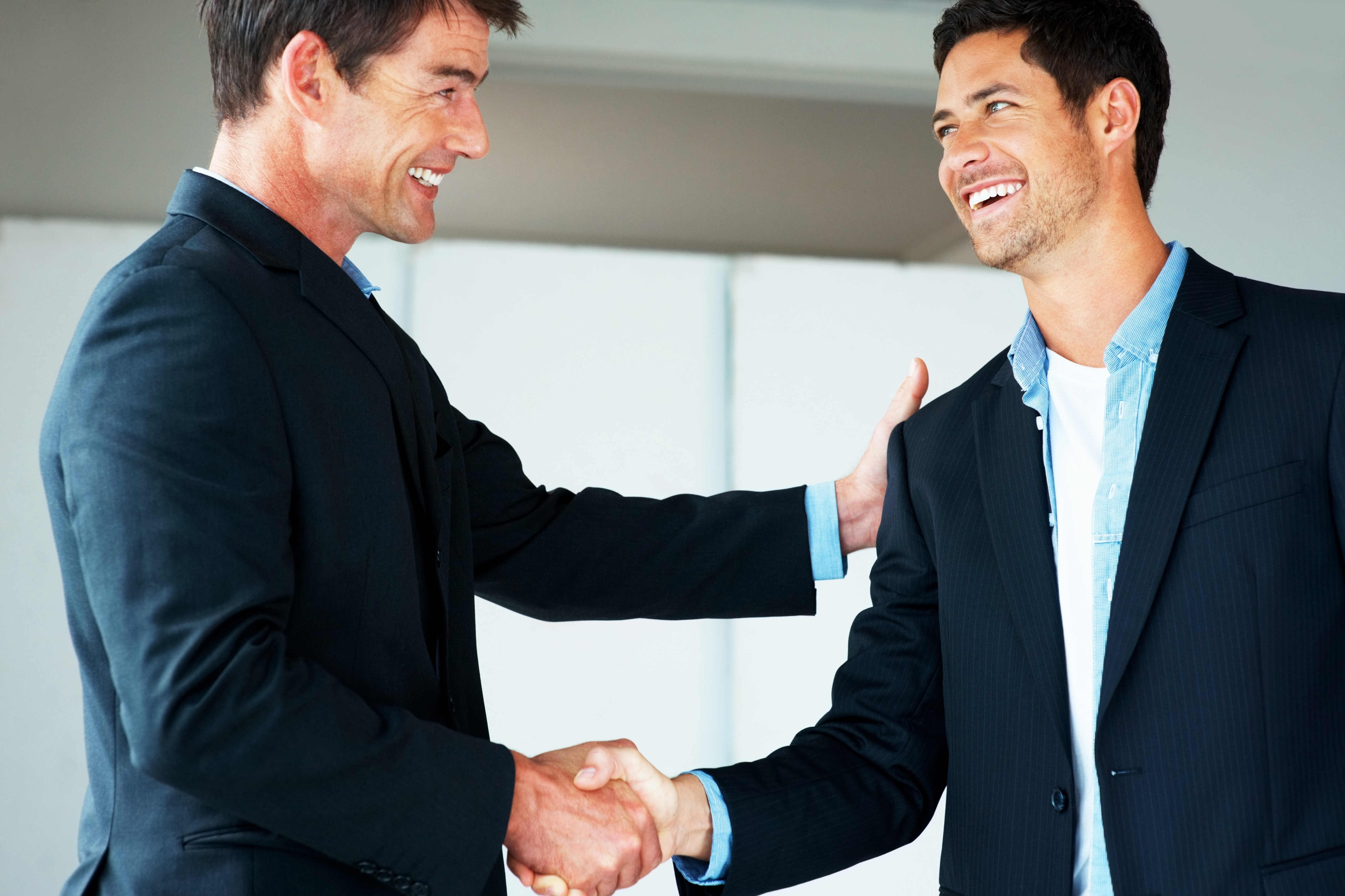 Portrait of successful business people shaking hands on a deal in office
