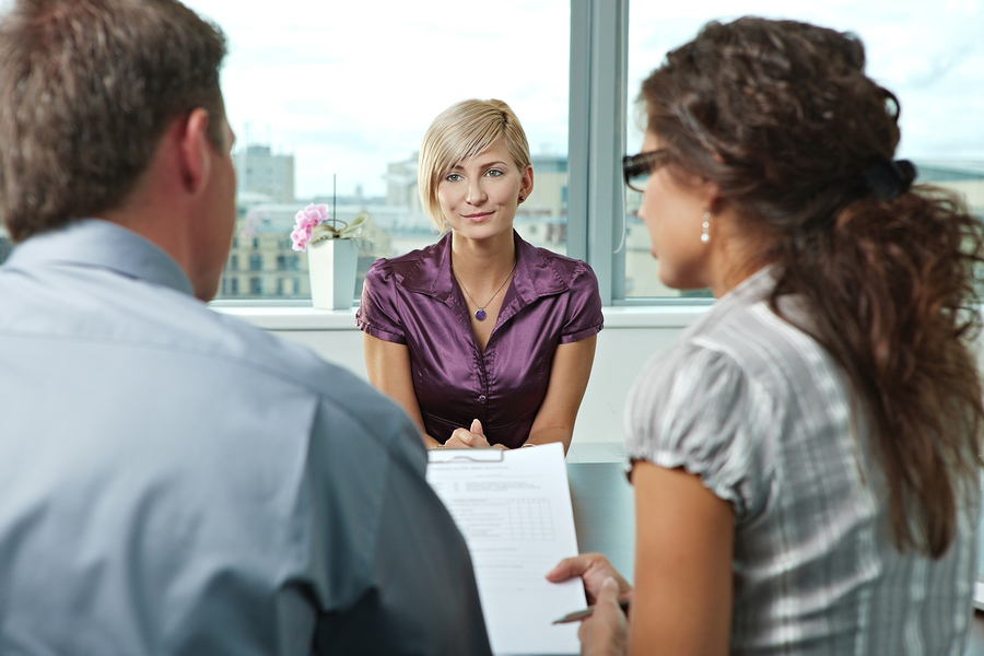 Attractive woman applicant talking during job interview. Over the shoulder view.